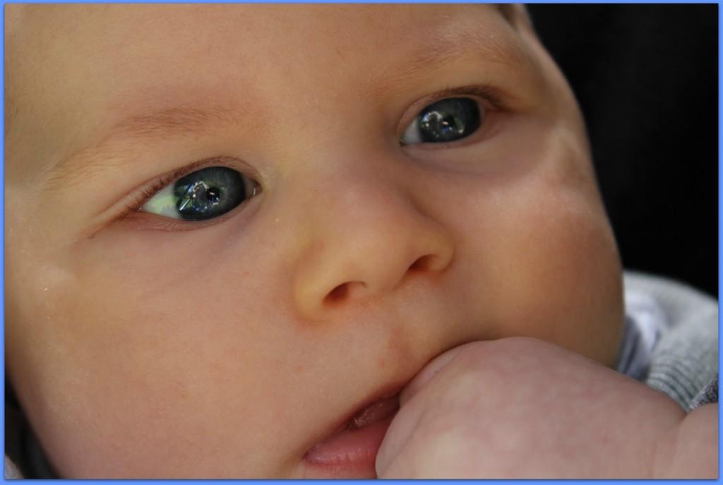 baby eyes sucking hand