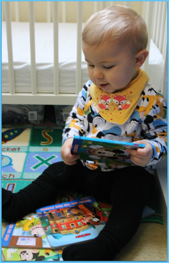 Caspian playing with the box set of books about Mickey Mouse and Friends from Parragon Books