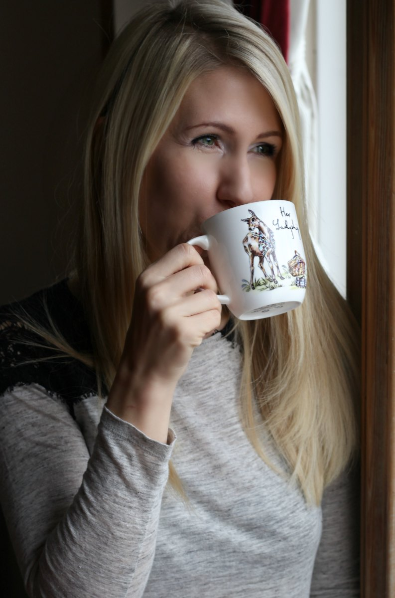 Woman drinking coffee from mug with stag print from QWERKITY