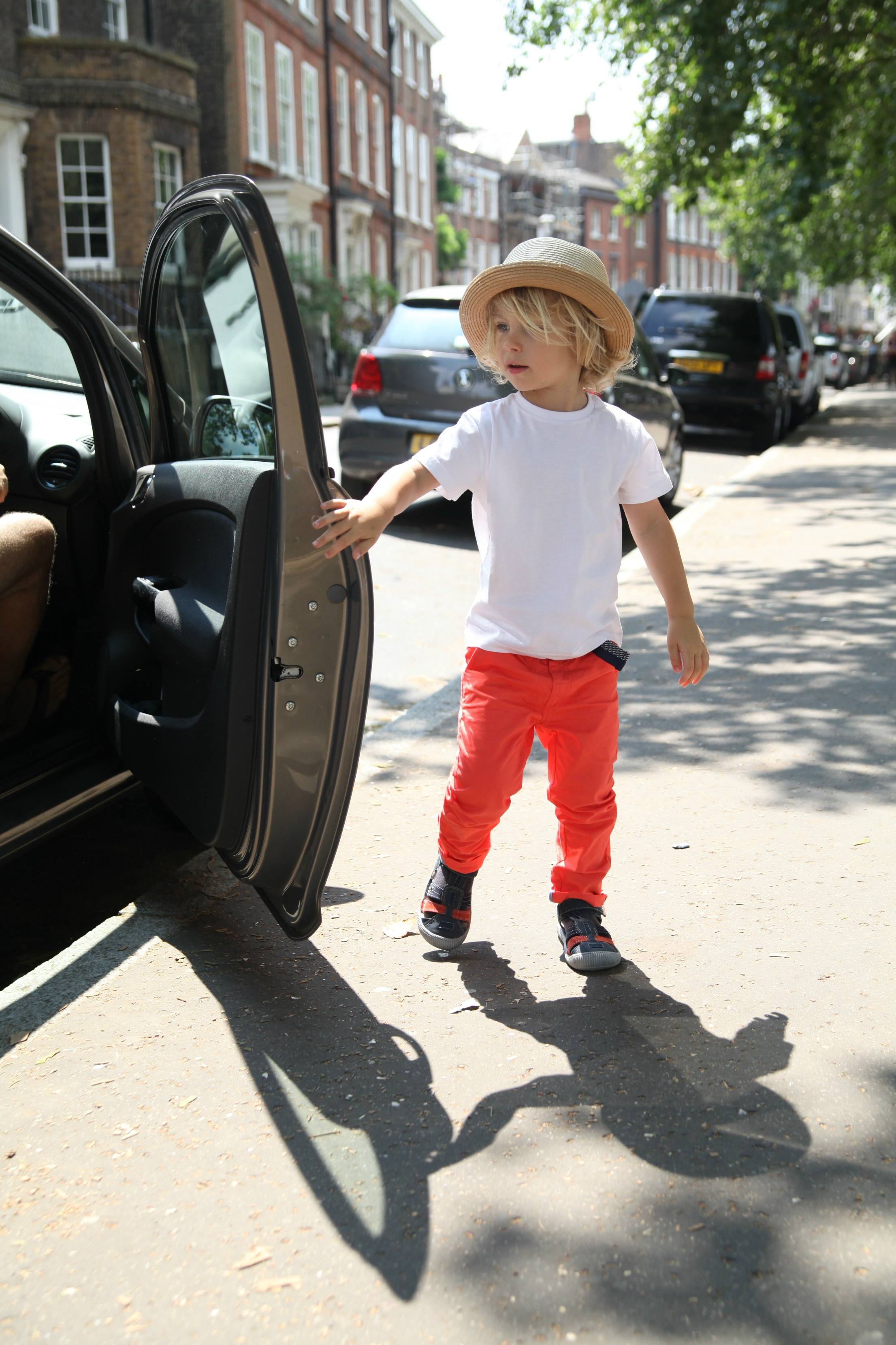 Boy opening car door dressed in Vertbaudet